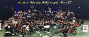 """Leuchtturm-Konzert mit vielen Kappelner Instrumental-SchülerInnen in den Reihen des Orchesters """"Sønderjylland-Schleswig-Pops"""" in der Mehrzweckhalle am 25.3.2018"""